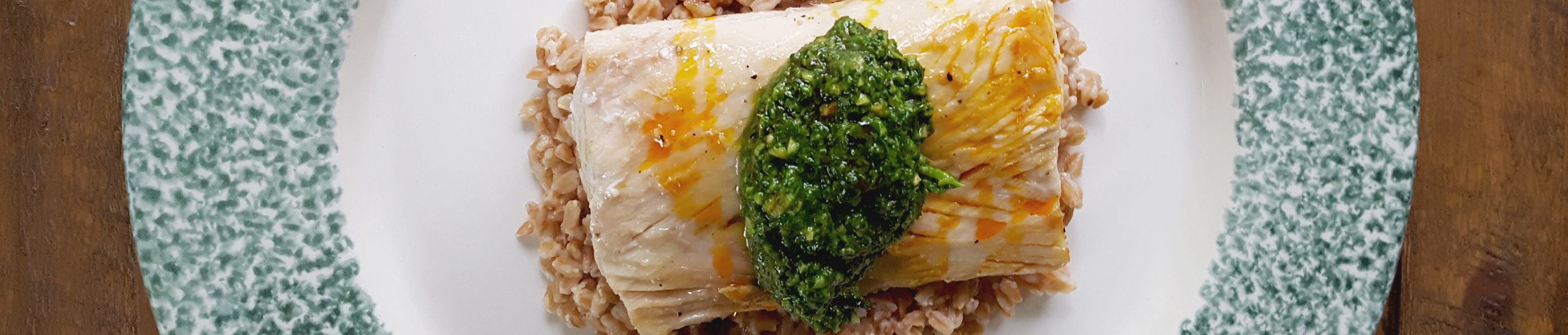 Fish topped with pesto served on a bed of rice